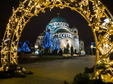 Church of Saint Sava or Saint Sava Temple  (Hram Svetog Save) and a park in front of the temple decorated with New Year's decorations on the Vracar plateau in Belgrade, Serbia, at night.