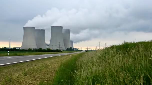 Nuclear power plant with four smoking chimneys in green nature meadows. Timelapse video.