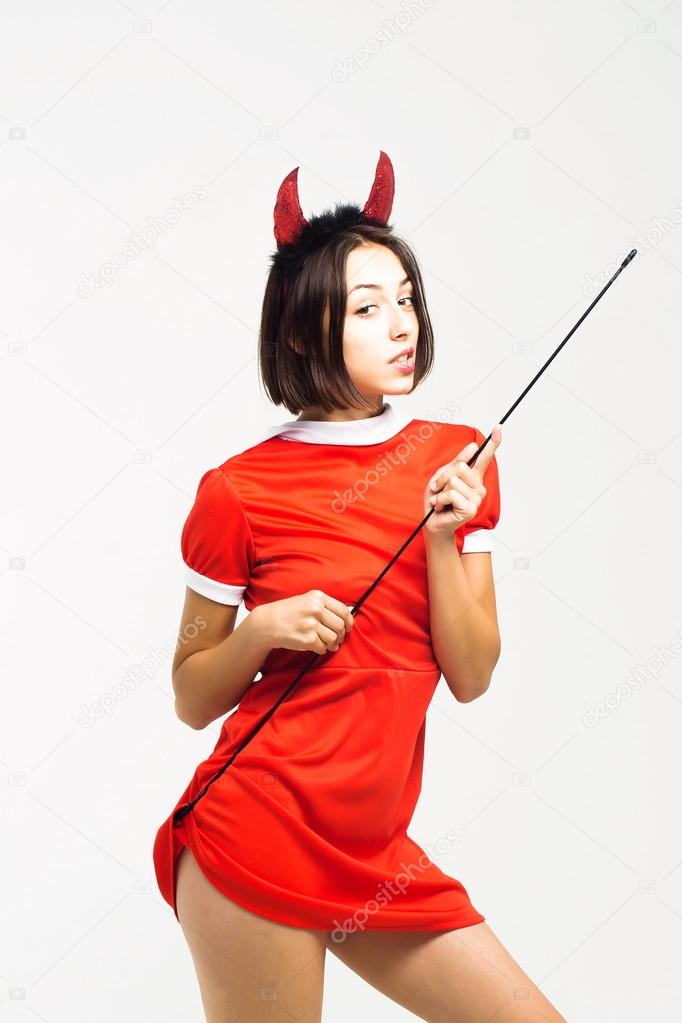 halloween sexy girl in devil antlers with stick stock photo