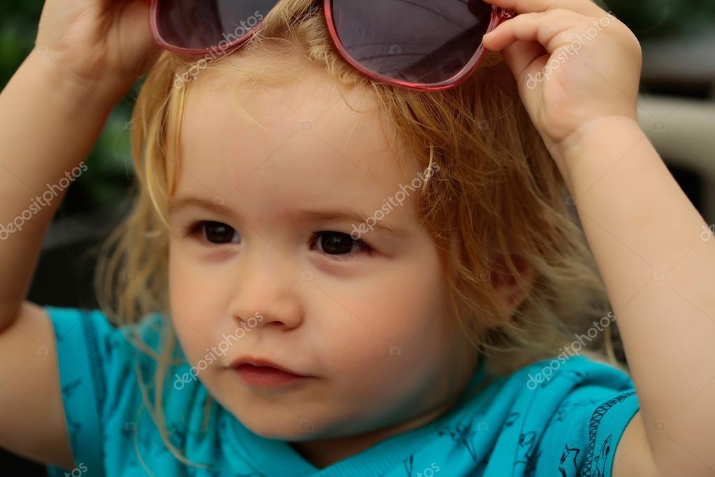bea316b3b4 Αστείο μωρό αγόρι παιδί με σγουρά ξανθά μαλλιά και γυαλιά ηλίου σε  καλοκαιρινή μέρα στο υπαίθριο καφέ — Εικόνα από ...