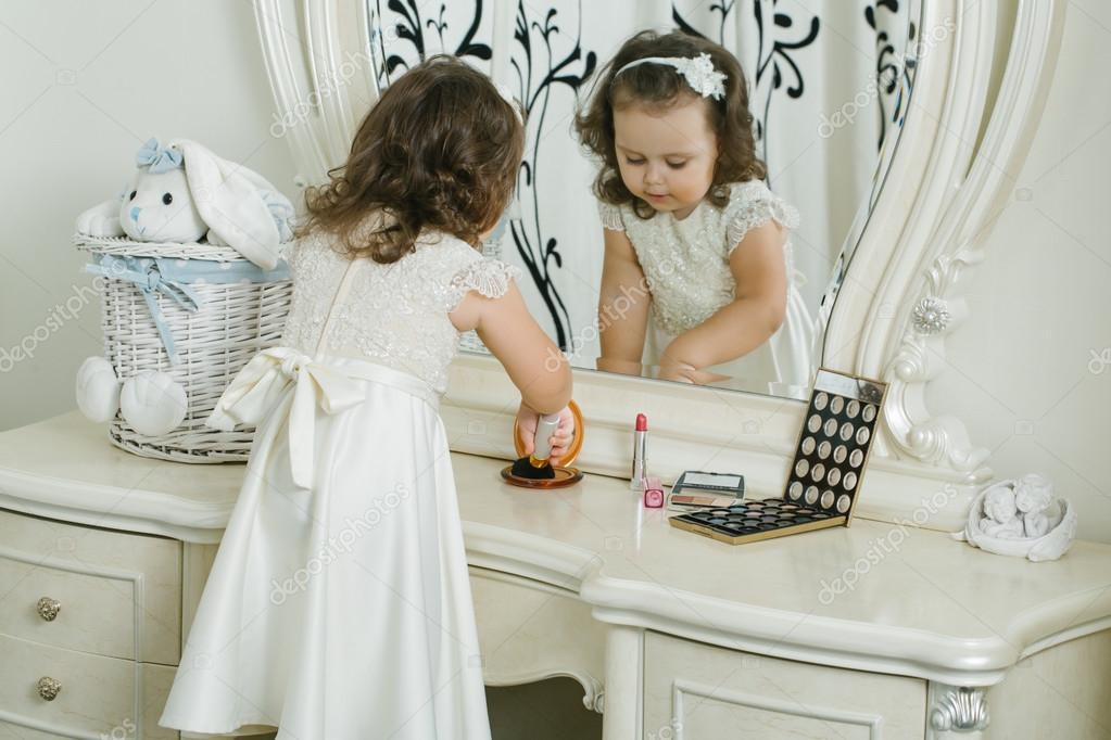 d889badabd18d Mignonne petite fille s applique à faire place devant le miroir. Adorable  bébé joue avec les produits cosmétiques — Image de ...