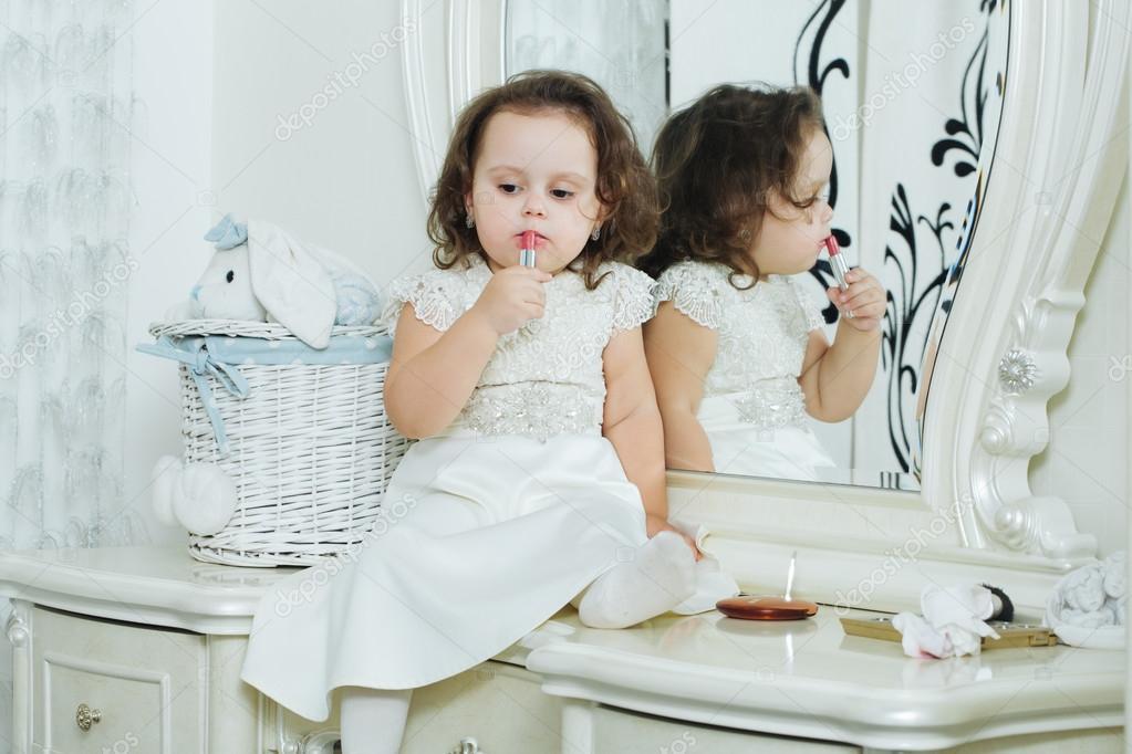 04bb840ecde7c Mignon bébé fille avec rouge à lèvres devant le miroir. Adorable petit  enfant joue avec le rouge à lèvres — Image de ...