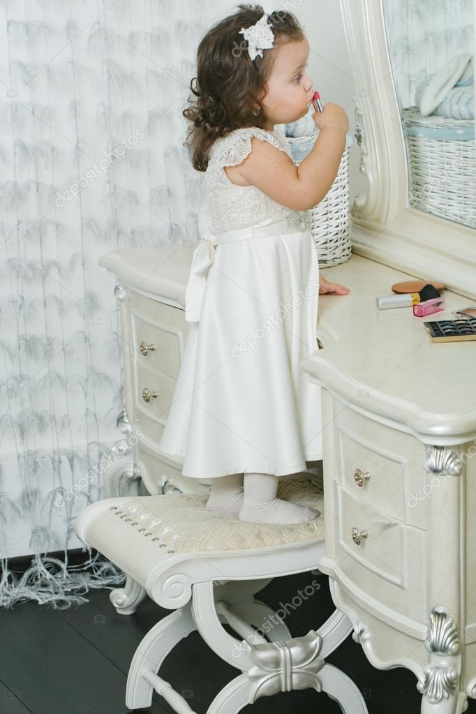 5a406d18c95e5 Mignonne petite fille joue avec rouge à lèvres devant le miroir. Adorable  bébé joue avec la trousse de maquillage — Image de ...