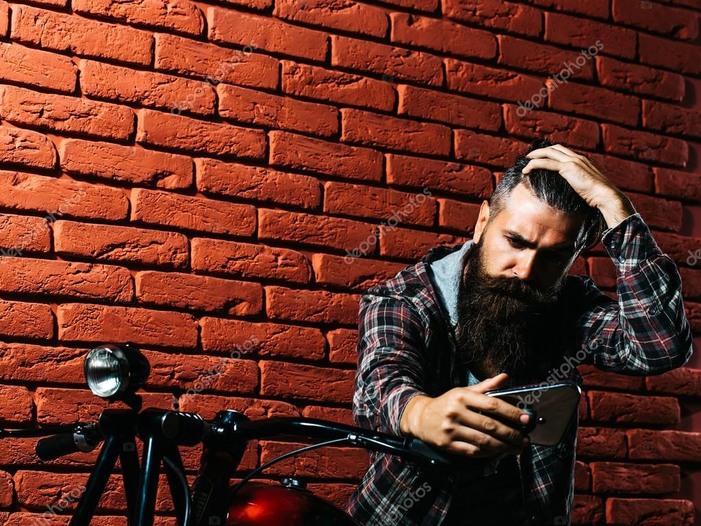 Uomo barbuto motociclista su una moto foto stock for Piani di caverna di garage uomo
