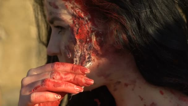 girl removes from the face zombies makeup on Halloween on background of wall