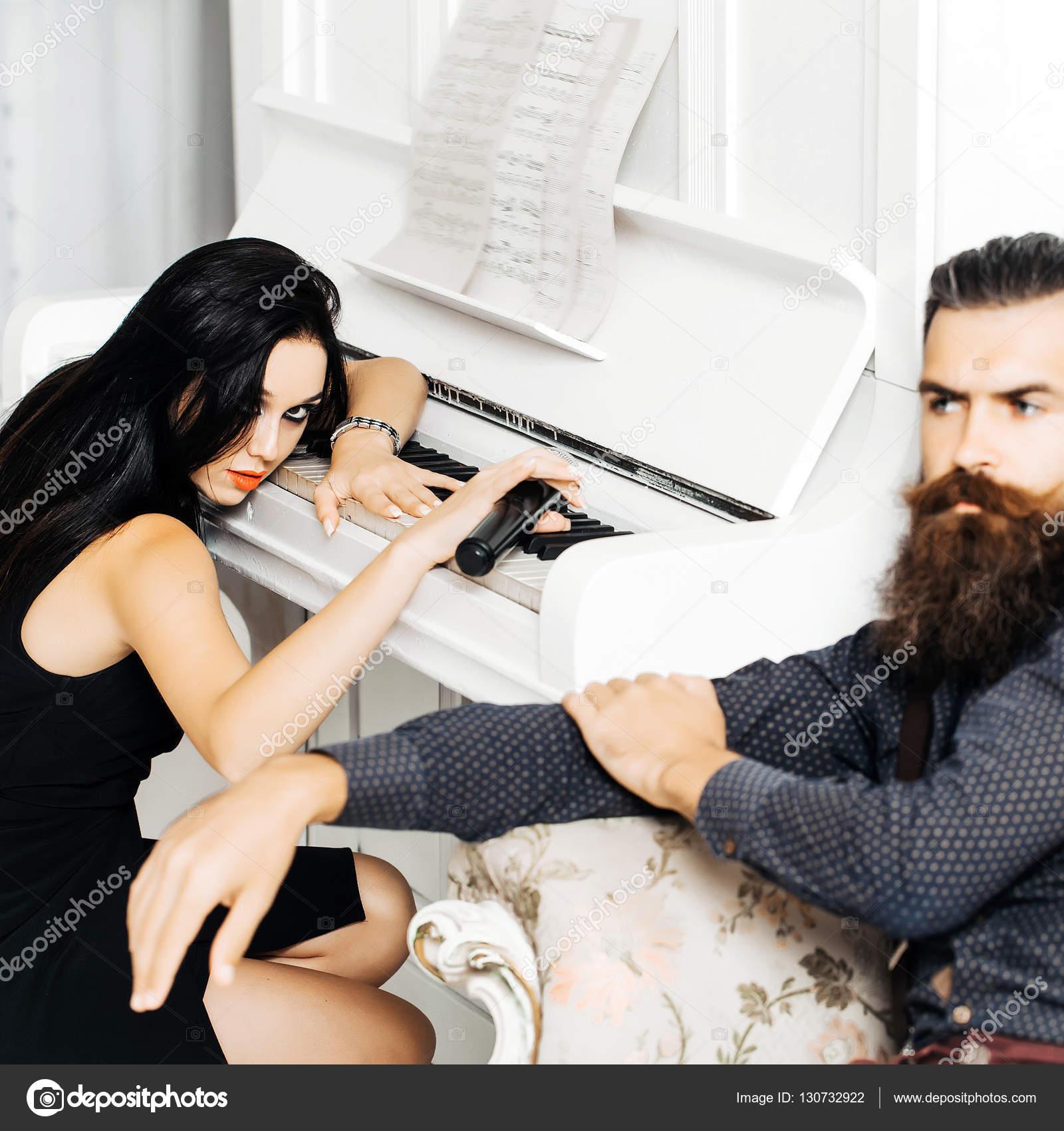 94283c072bca Muito sexy jovem garota com longos cabelos escuros vermelho batom no vestido  preto com microfone na mão se senta no piano branco e bonito homem barbudo  na ...
