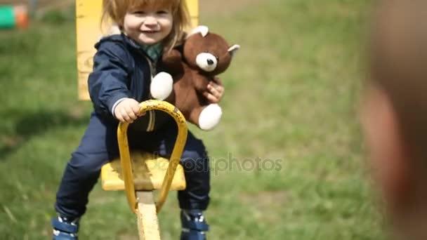 Boldog gyerek egy hinta, egy barna mackó