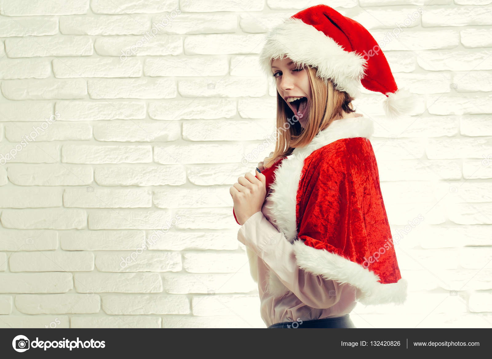 fc4a477f92 Young sexy new year woman or cute smiling girl with pretty happy face  winking in red christmas santa claus holiday hat and coat on white brick  wall ...