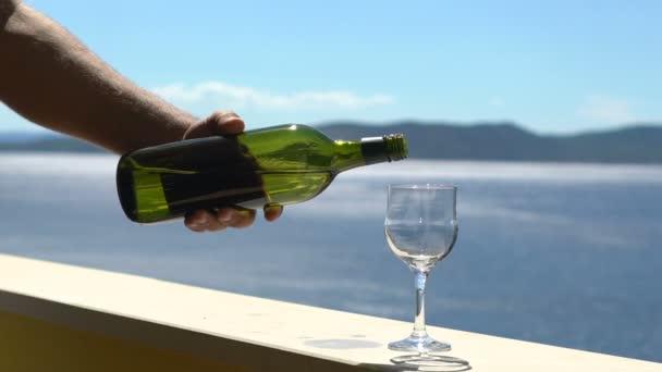 Mann gießt Weißwein in ein Glas vor dem Hintergrund einer Meereslandschaft, sonniger Sommertag auf See, Zeitlupe