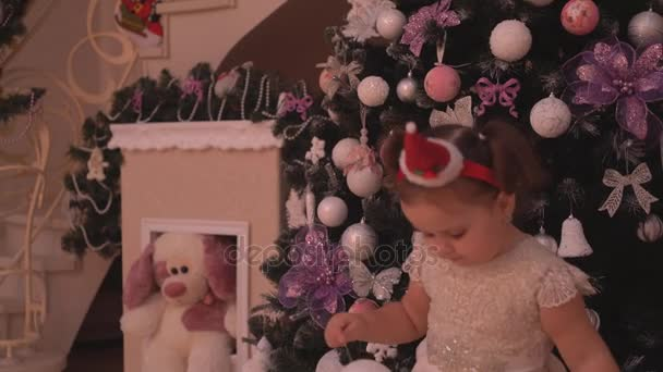 Kis lány, karácsonyi díszek egy elf cap-ban játszik