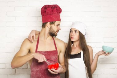 Handsome man or muscular cook, baker, with sexy, muscle torso, body, with biceps, triceps beats dough by whisk with pretty girl or beautiful woman, cute helper on kitchen wall stock vector