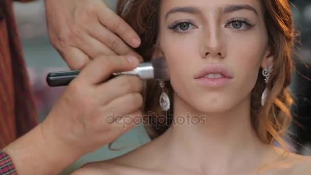 Makeup artist applies skintone. Beautiful woman face. Perfect makeup start with skincare foundation