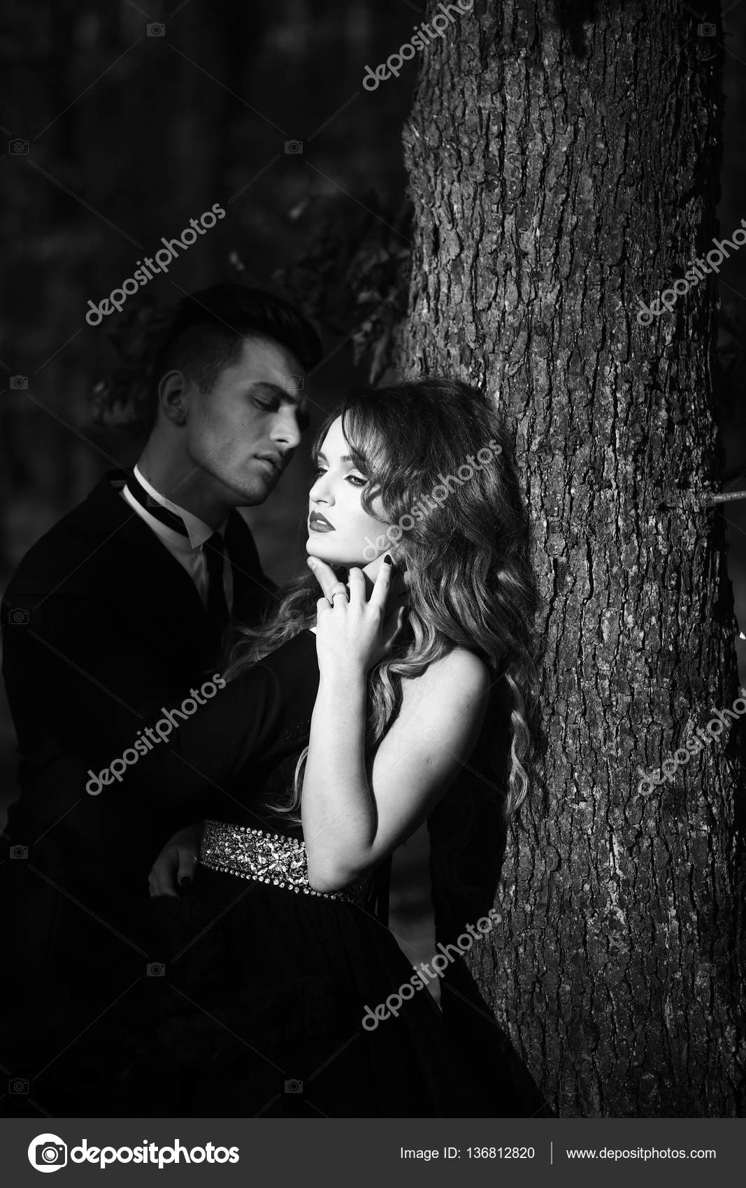 887d55ccb22f7 Young couple of handsome man in suit and bow with pretty sexy woman in elegant  evening dress with skirt and long curly hair near tree in deep forest, ...