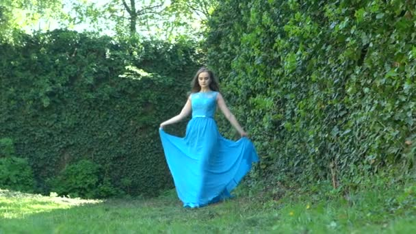 Slow motion: Girl with long hair in a blue dress walk in the green garden. Beautiful gait of a young woman in a long dress
