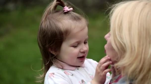 Dcera dává její matka velké objetí. Roztomilé batole hraje s matkou