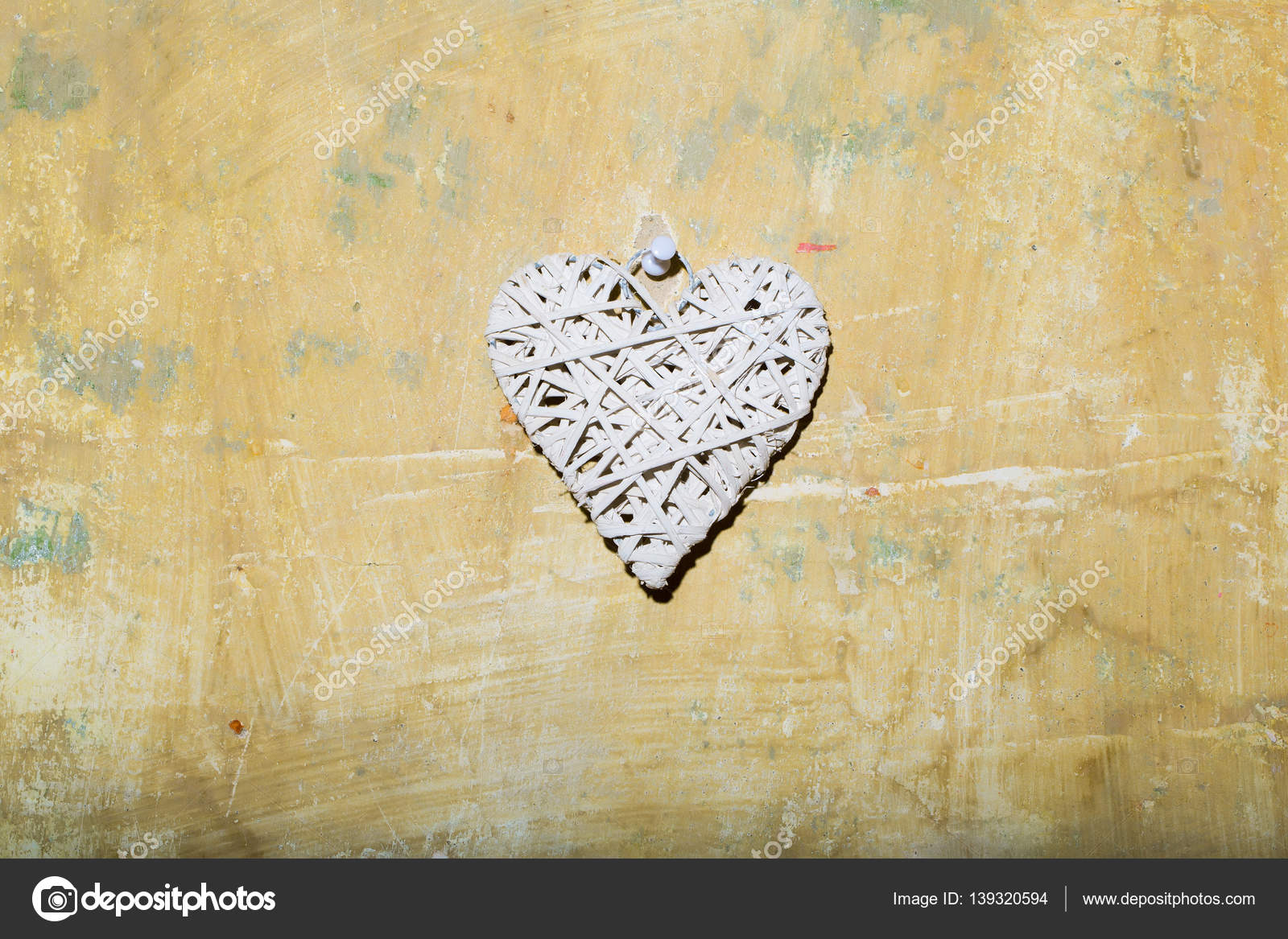 abstract valentines day heart on yellow textured wall, copy space ...