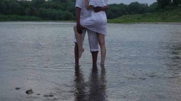 Couple of lovers embracing in summer river barefoot. Young man and woman in love enjoy each other in the water. Interracial couple in the river