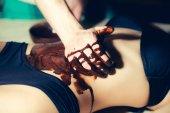Fotografie weibliche sexy Bauch und männliche Hände auf Schokoladen-massage