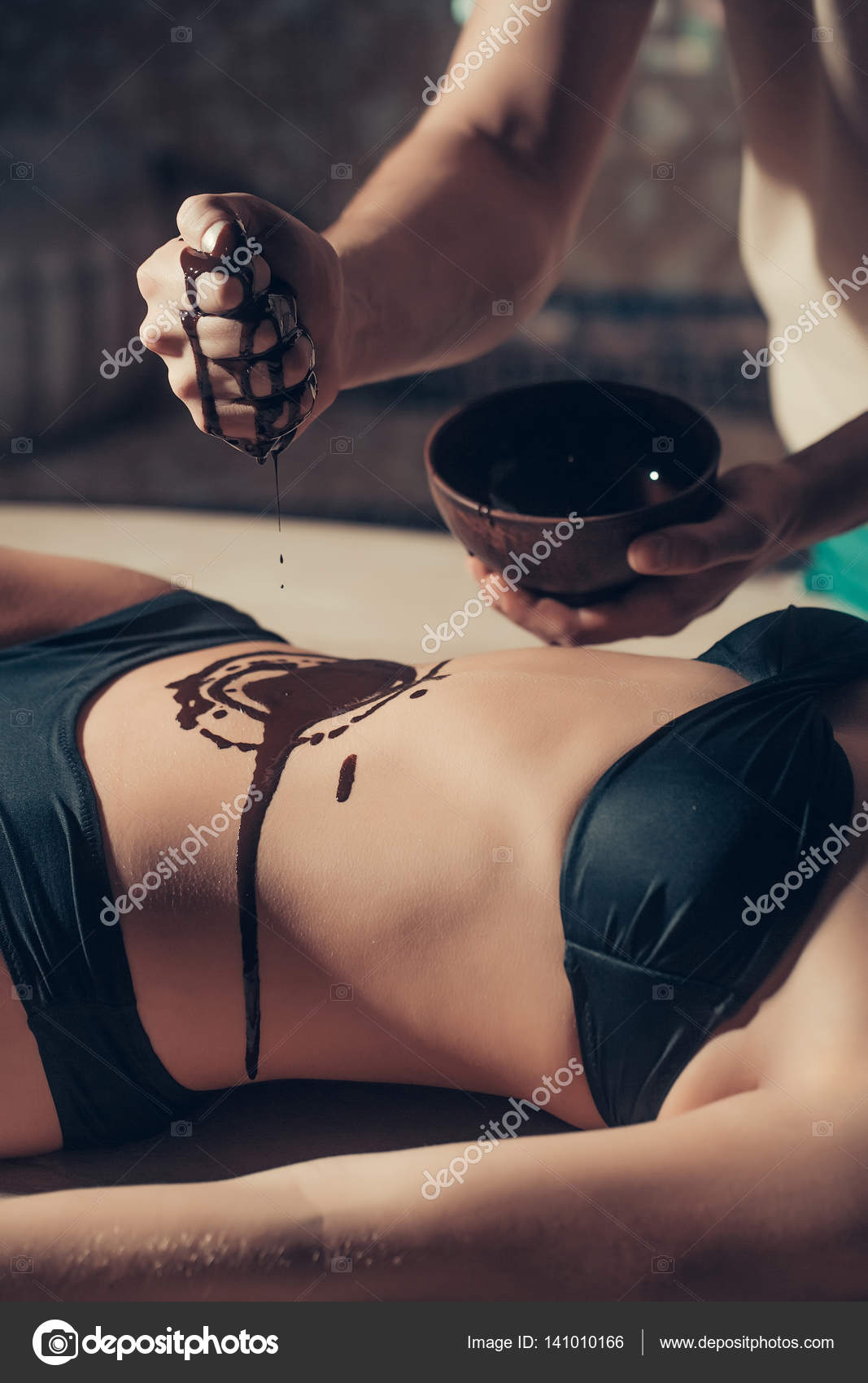 Female sexy belly and male hands on chocolate massage ...