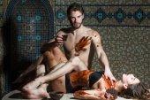 muskulöser Mann und sexy Frau essen nach Salon-Massage Schokolade
