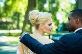 Milující ženich se dotýká ramene rozkošná nevěsta