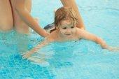 Roztomilý chlapeček se učí plavat s pomocí matky