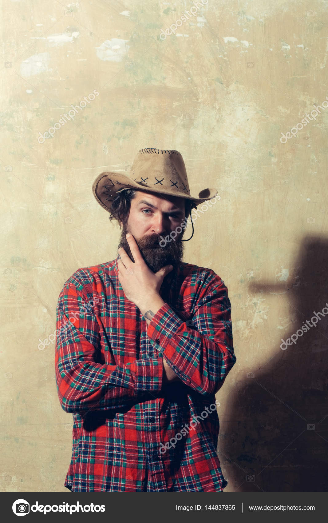 d9c751e4d21 Bearded man in cowboy hat and black shadow on wall — Stock Photo ...