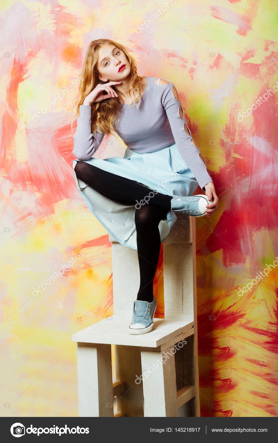 Bella da blu legno e sedia ragazza in gonna in tennis scarpe su OrqwrYAtxy