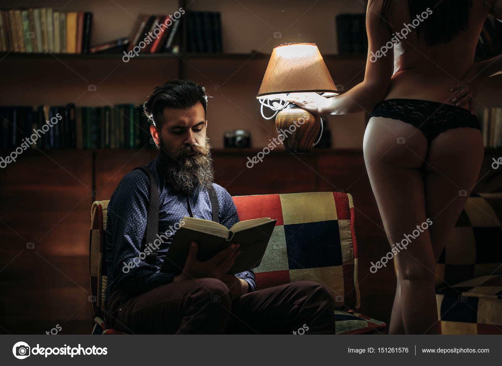 b9beaf8bd8a Young couple of handsome bearded man sitting on armchair in library reading  book and pretty cute girl or woman in black lingerie with sexy buttocks and  body ...