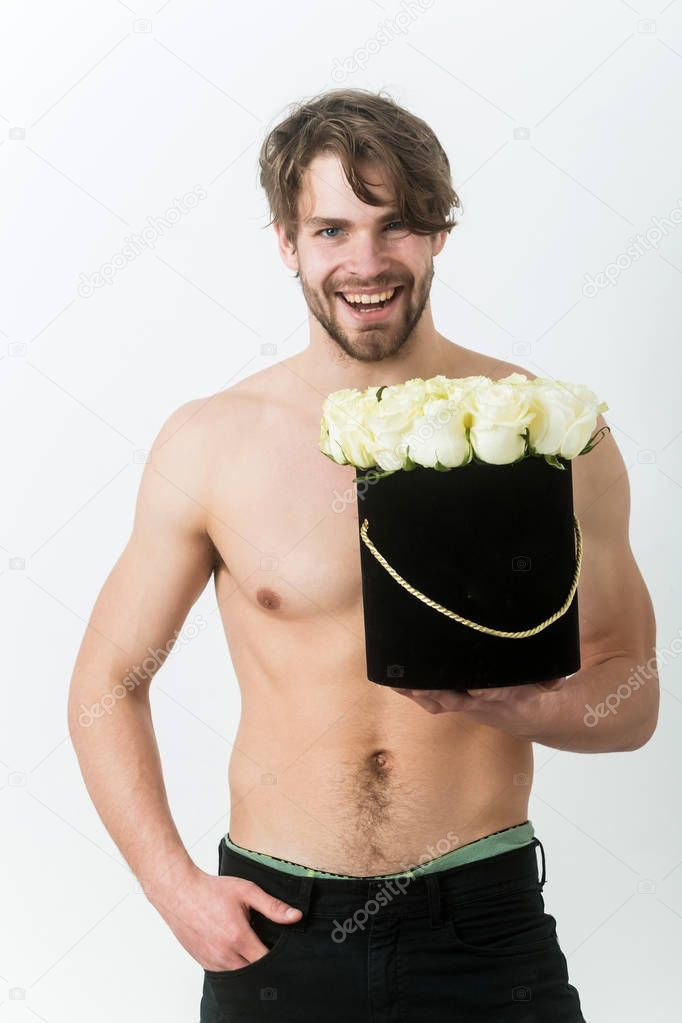 man smiling with fresh roses in black box