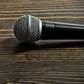 Fotografie professionelles Mikrofon auf hölzernen Hintergrund, Textfreiraum