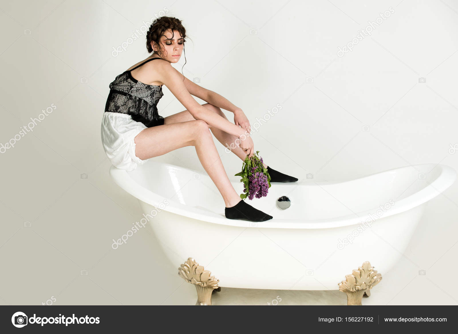 Vasca Da Bagno Piccola Vintage : Donna che si siede sulla vasca da bagno vuota vintage con mazzo