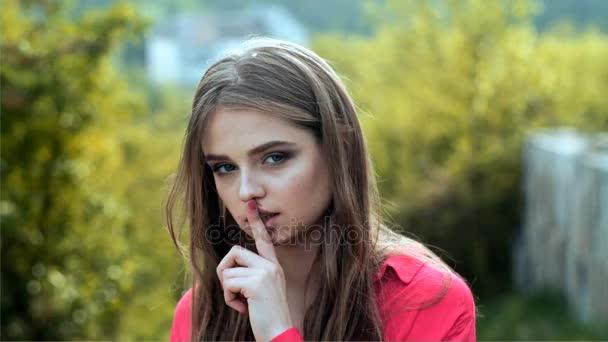 Dívka drží prst rtům. Raddle mladé dívky. Mladá dívka na přírodu s dlouhými vlasy. Emoce, flirtování, sexy v ústech. Žena v Růžové tričko, žádá o ticho, klid. Atraktivní studentka