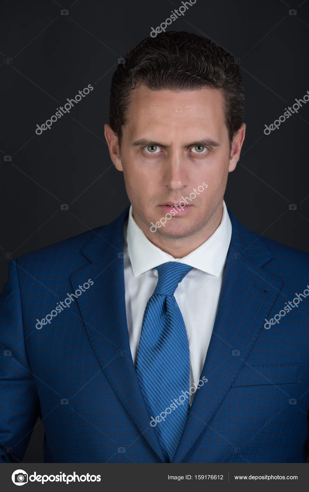 Businessman Posing In Elegant Blue Jacket And Tie Stock Photo