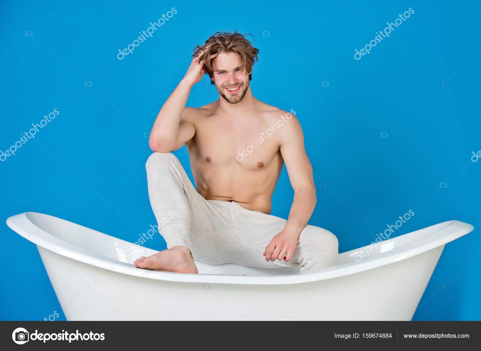 Giovane bello con corpo muscoloso che si siede nella vasca da bagno bianca foto stock - Foto nella vasca da bagno ...