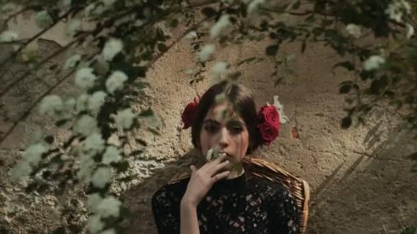 Krásná dívka s červenými růžemi její vlasy a červené rtěnky drží v ruce květiny a sny. Mladá žena, které představují profesionální model. Jarní květy stromů. Cigarety s příchutí. Přestat kouřit