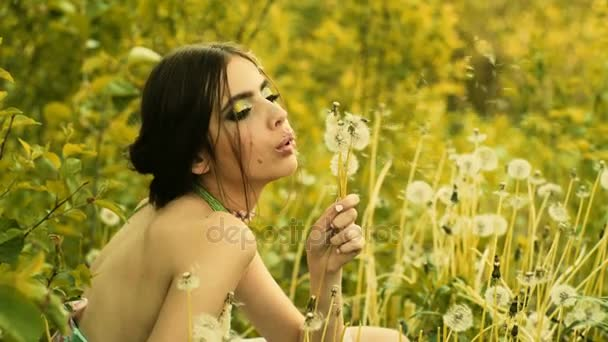 Dandelions and young girl with green eye shadow, beautiful makeup for spring. Spring in the field, outside the city, a lot of grass and flowers. Girl blowing on dandelion seeds in summer outdoors