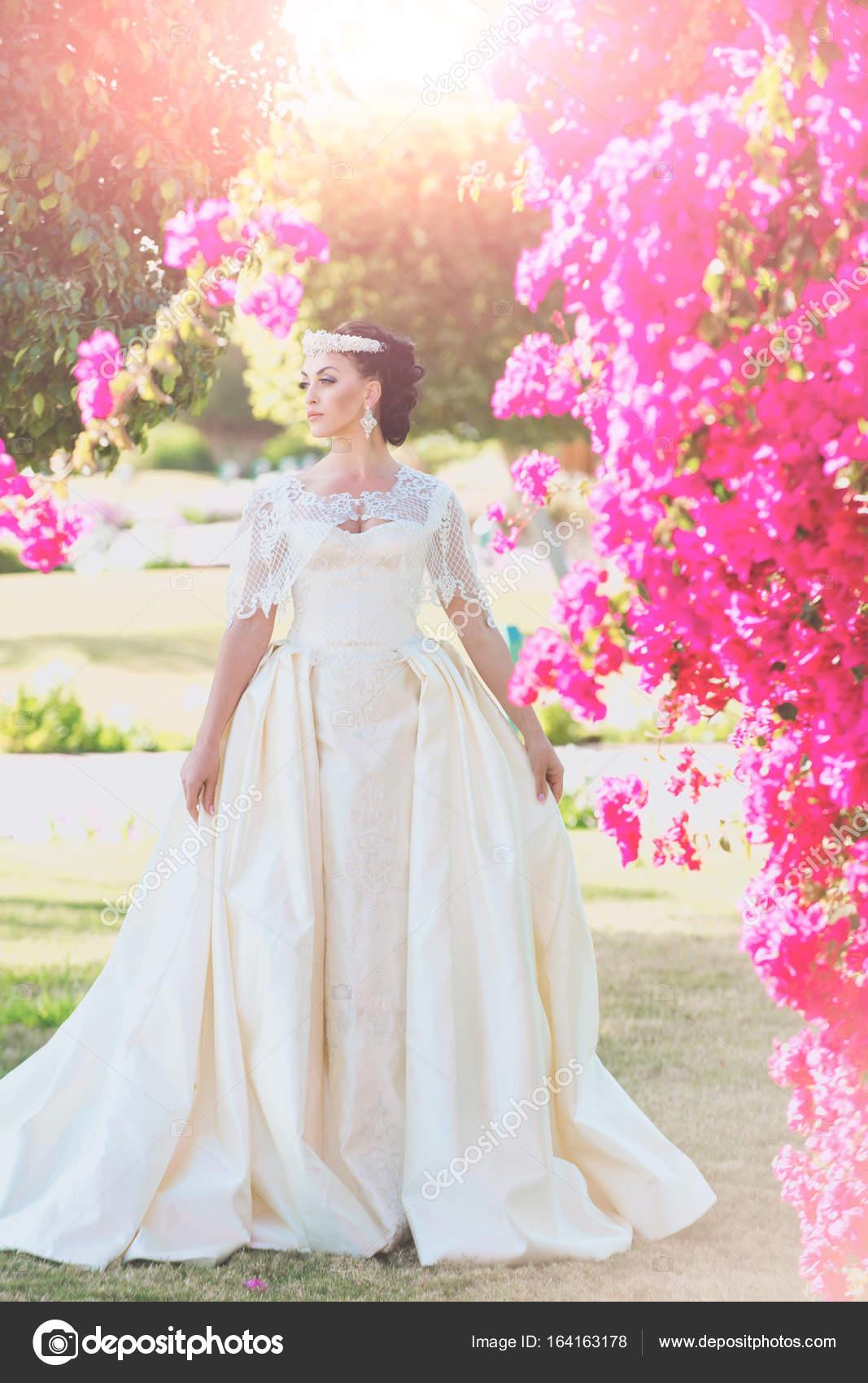 Novia en blanco vestido de novia posando cerca arbusto color de rosa ...