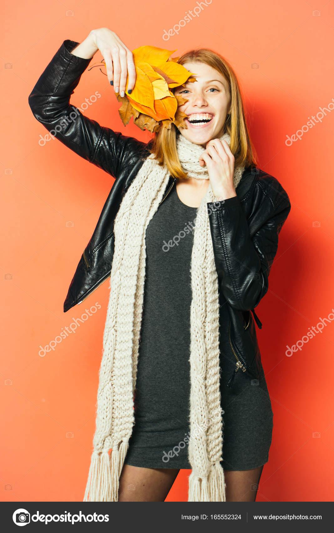 Γυναίκα με φθινοπωρινά φύλλα σε δερμάτινο μπουφάν. Κορίτσι με πορτοκαλί  φύλλα σε πορτοκαλί φόντο. Holiday σεζόν και το φθινόπωρο. Ομορφιά και τη  μόδα. 6e29a2c9fb1