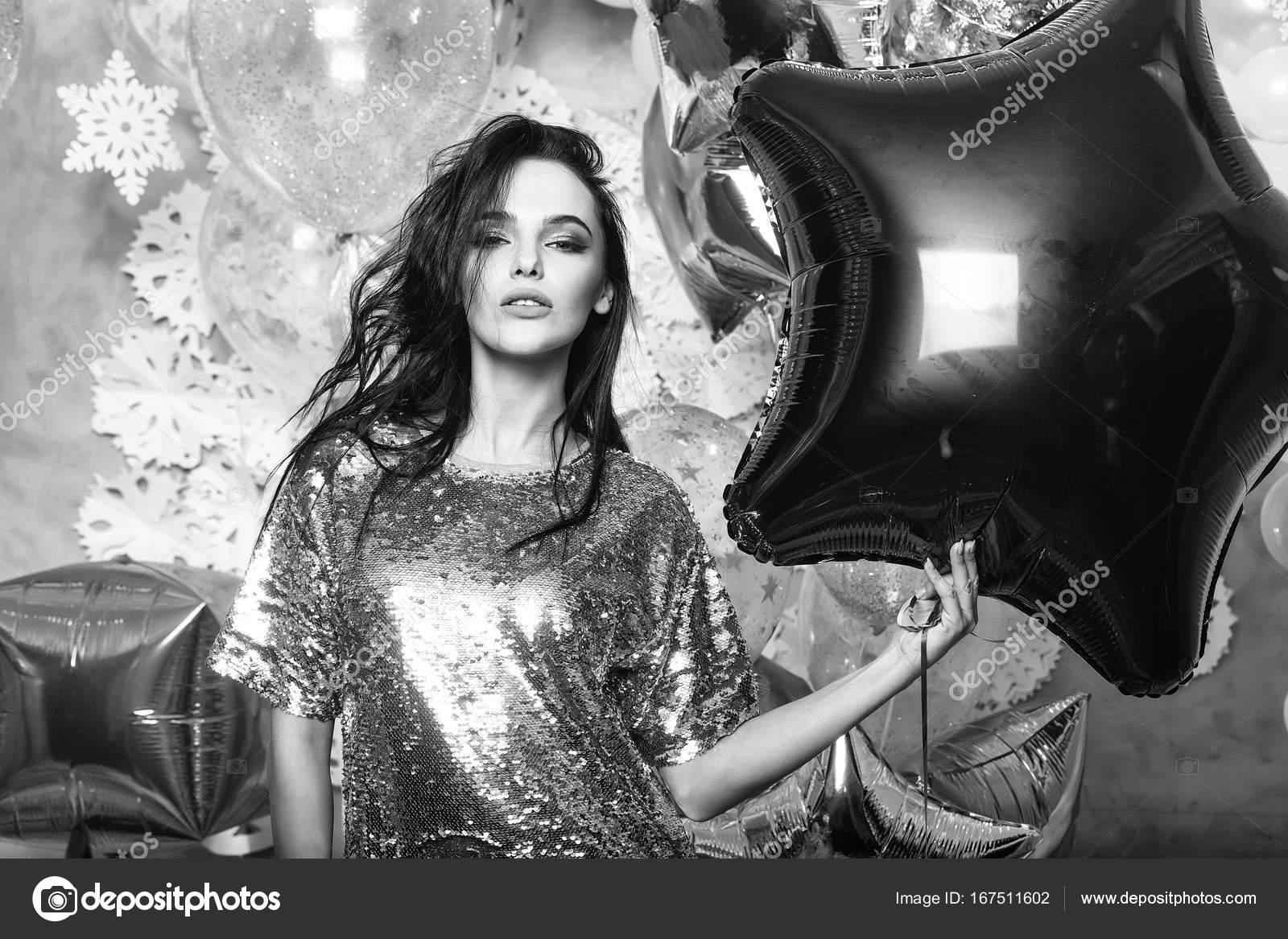 Sexy vrouw in zilveren pailletten jurk met feestelijke ballonnen