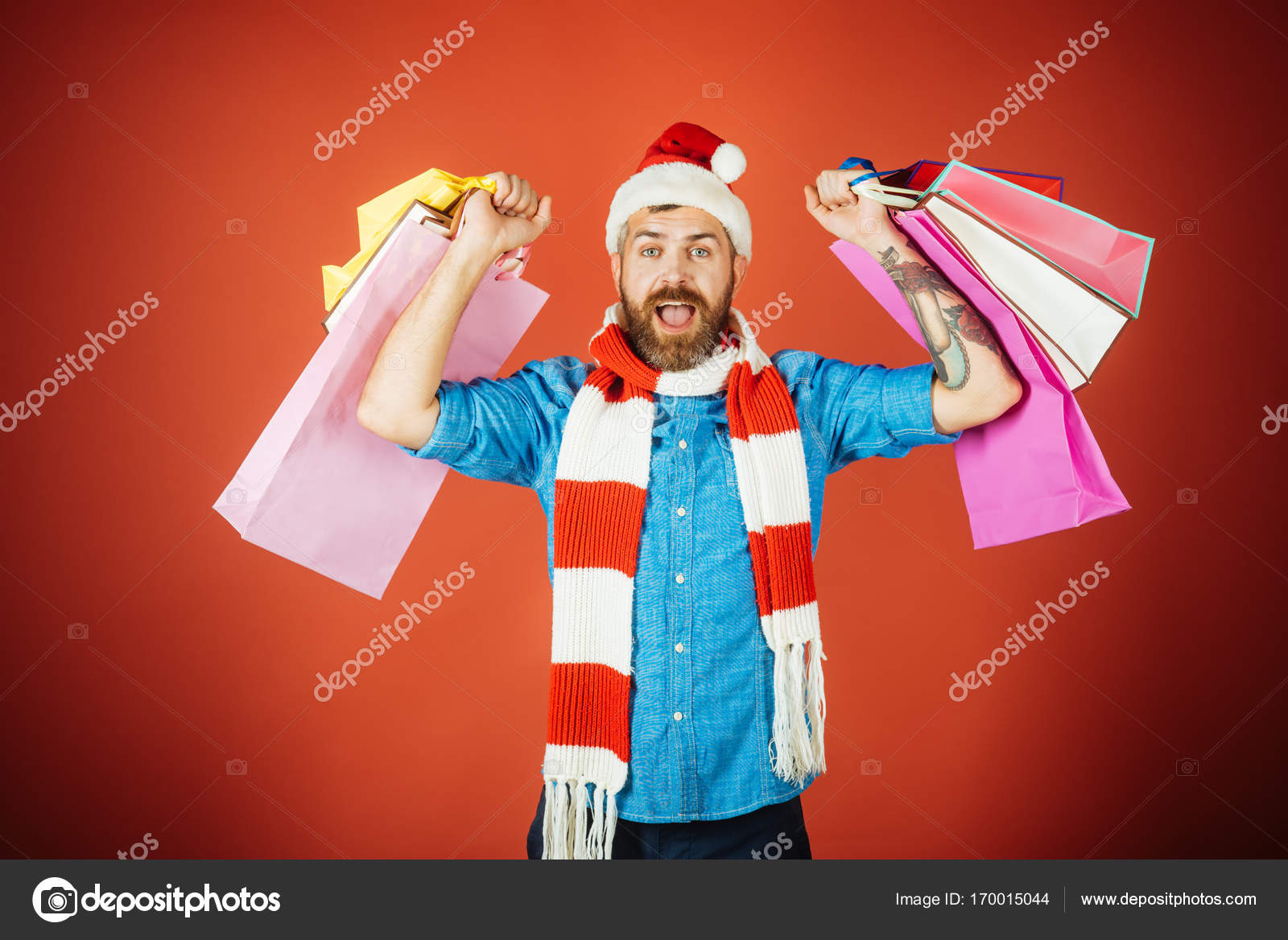 0547f5683ec99 Christmas man shopper happy shout in santa hat and scarf– stock image