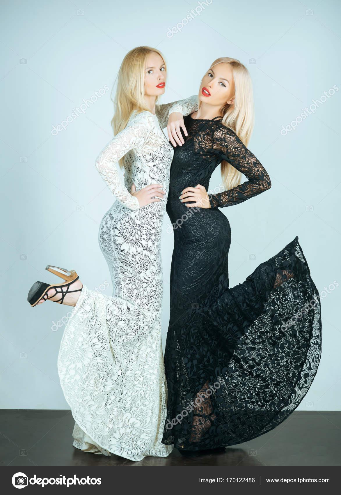 e00def5c89f9 Ragazze con capelli lunghi biondi e trucco labbra rosse. Modelli glamour su  priorità bassa blu. Donna che posa in abiti di pizzo bianco e nero.