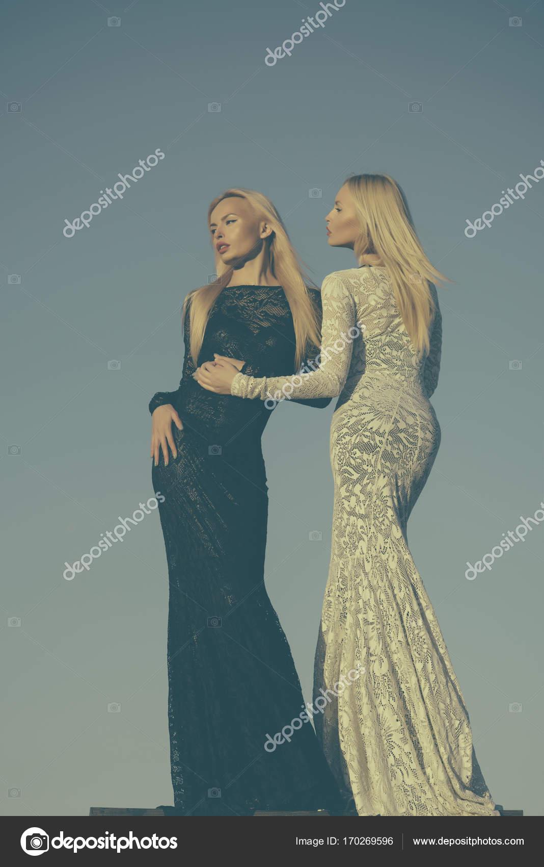 85707702b9f Γυναίκες που φορούν μαύρα και άσπρα φορέματα. Μόδα και ομορφιά. Απόφαση  επιλογής, και το μέλλον. Δύο κορίτσια με μακριά ξανθά μαλλιά ποζάρει στο  γκρίζο ...