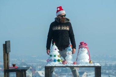 Man looking at snowmen and snow xmas tree on table