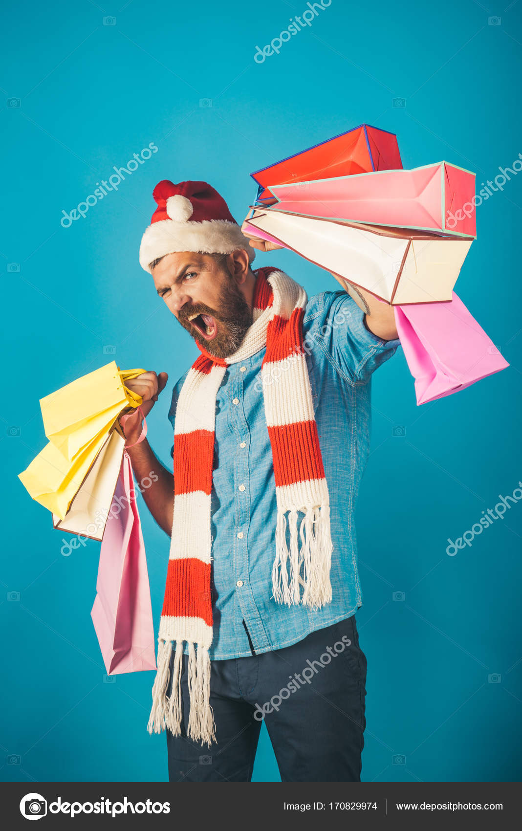 4432d6e166f18 Christmas man shopper happy shout in santa hat and scarf. Hipster hold  shopping bags on blue background. New year