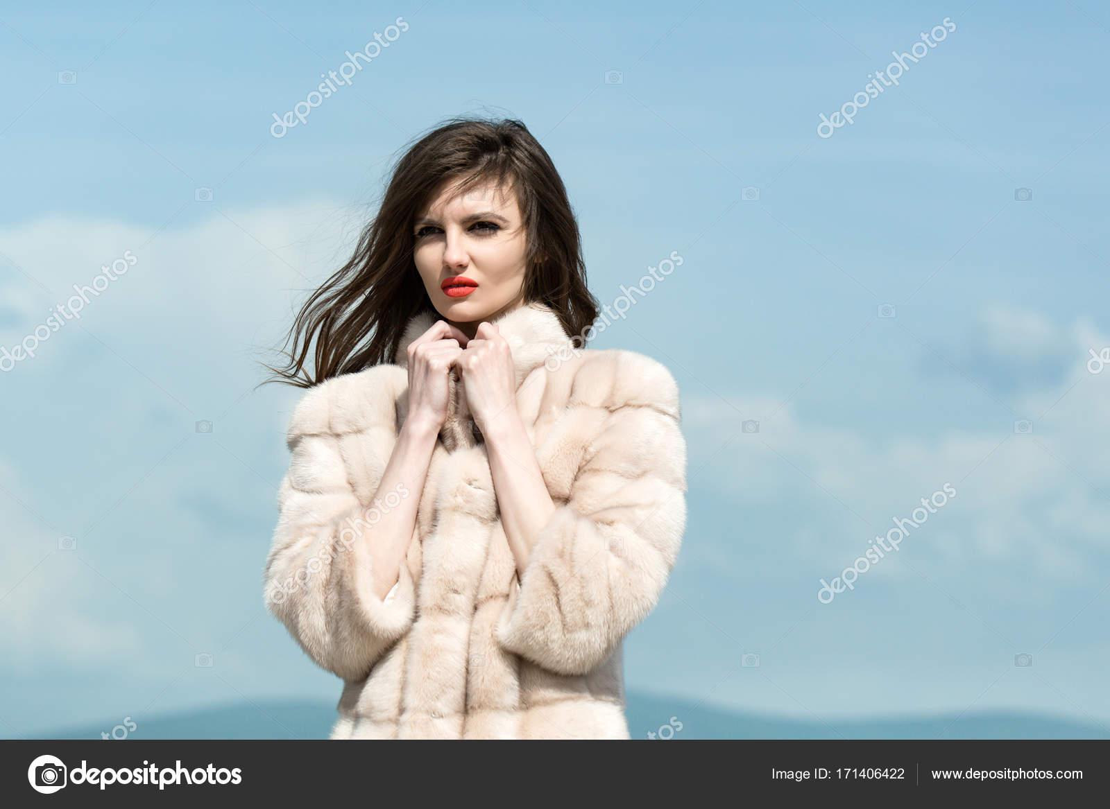 Ragazza in cappotto di pelliccia alla moda in inverno. Donna con capelli  lunghi del brunette e labbra rosse in cappotto. Modello di modo sul fondo  del cielo ... b00a651aaef