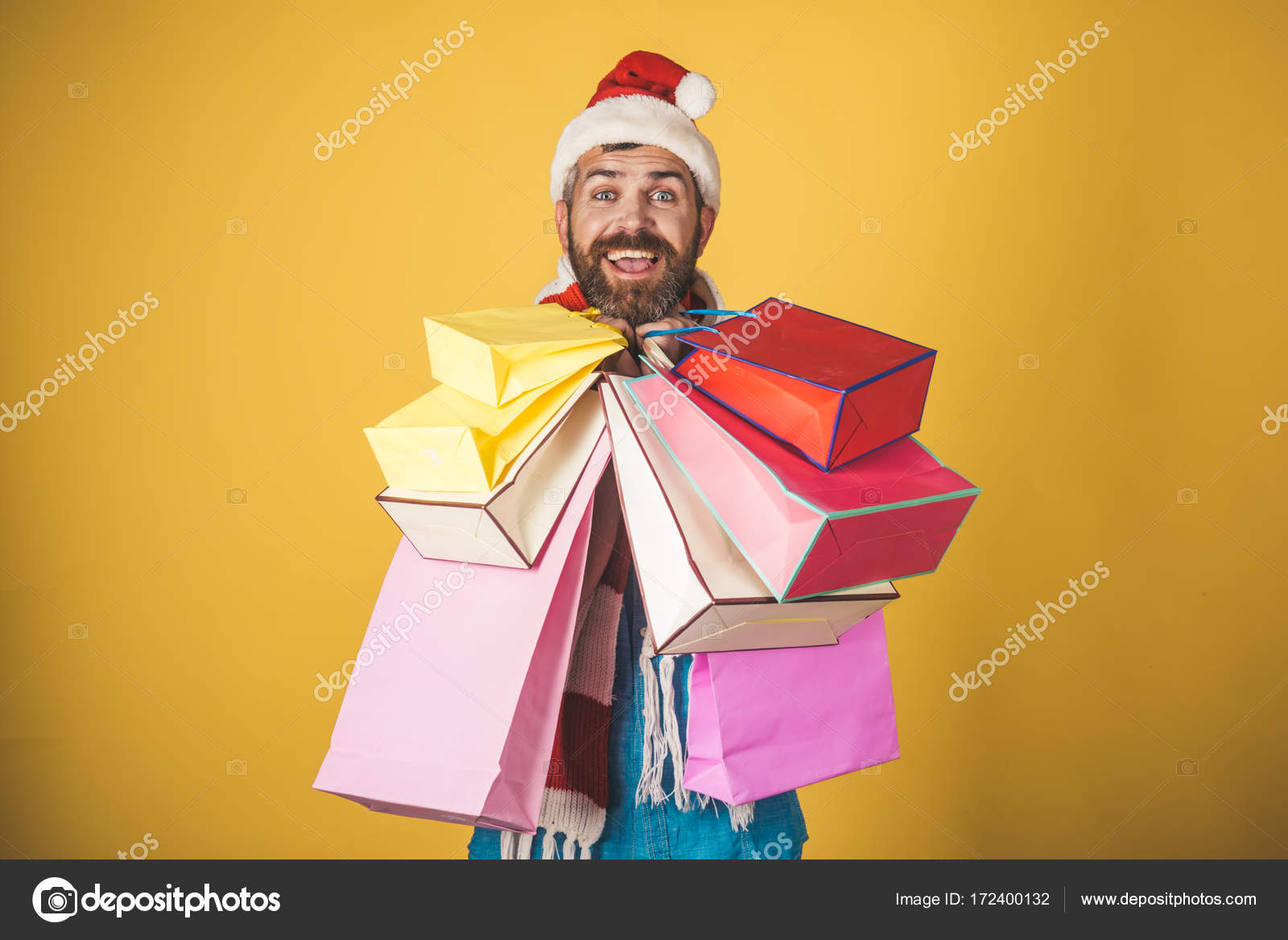 386d5019f24a7 Christmas man hold shopping bags on yellow background. Hipster shopper smile  in santa hat and scarf. Black friday sale concept. Winter holidays  celebration.