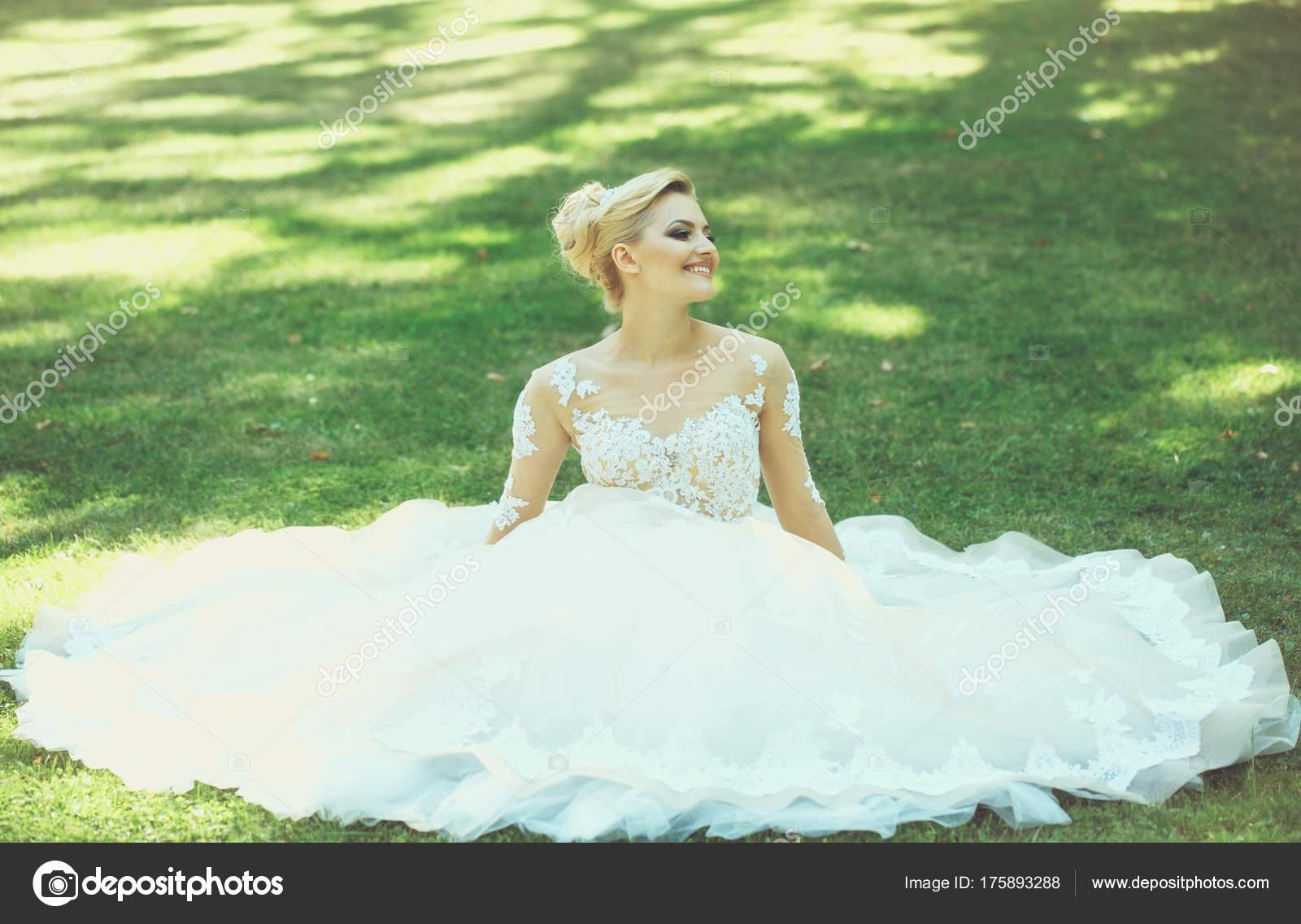 Glücklich niedliche Braut in weiß Hochzeit Kleid auf dem grünen ...