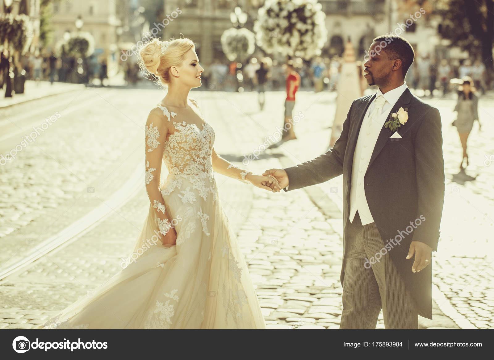 Schöne afrikanische Bräutigam und niedliche Braut an den Händen ...