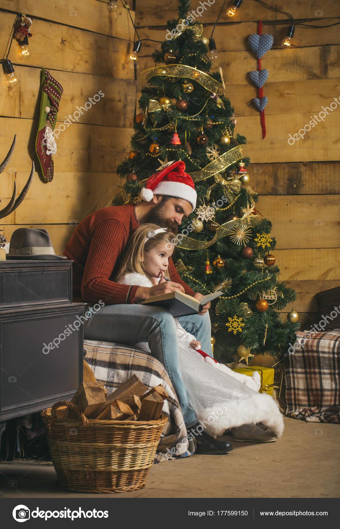 Natale felice uomo e bambina piccola con padre barbuto in cappello di Babbo  Natale rosso leggere Prenota all albero di Natale b790b8391cba